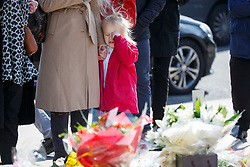 © Licensed to London News Pictures. 25/03/2017. London, UK. A child pays her respects to the victims of Westminster terror attack in Parliament Square, London on 25 March 2017. Photo credit: Tolga Akmen/LNP