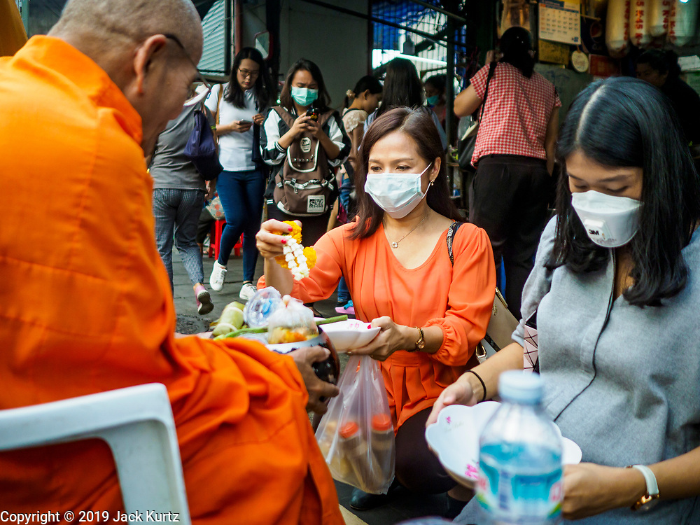 31 JANUARY 2019 - BANGKOK, THAILAND:   Women wearing breathing masks because of Bangkok's air pollution present food to a monk in Bangkok. The Thai government has closed more than 400 schools for the rest of the week because of high levels of pollution in Bangkok. At one point Wednesday, Bangkok had the third highest level of air pollution in the world, only Delhi, India and Lahore, Pakistan were worst. The Thai government has suspended some government construction projects and ordered other projects to take dust abatement measures. Bangkok authorities have also sprayed water into the air in especially polluted intersections to control dust. Bangkok's AQI (Air Quality Index) Thursday morning was 180, which is considered unhealthy for all people.     PHOTO BY JACK KURTZ