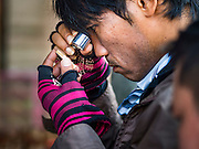 27 NOVEMBER 2015 - BANGKOK, THAILAND:  A man uses a jeweler's loupe to look at an amulet on Maharat Road in Bangkok. Hundreds of vendors sell amulet and Buddhist religious paraphernalia to people in the Amulet Market, a popular tourist attraction along Maharat Road north of the Grand Palace near Wat Maharat in Bangkok. Bangkok municipal officials announced that they are closing the market and forcing vendors to relocate to an area about one hour outside of Bangkok. The closing of the amulet market is the latest in a series of municipal efforts to close and evict street vendors and markets from areas that have potential for redevelopment. The street vendors will be evicted from the area by Sunday, Nov. 29.   PHOTO BY JACK KURTZ