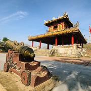 A cannon and pagoda outside the moat at the Imperial City in Hue, Vietnam. A self-enclosed and fortified palace, the complex includes the Purple Forbidden City, which was the inner sanctum of the imperial household, as well as temples, courtyards, gardens, and other buildings. Much of the Imperial City was damaged or destroyed during the Vietnam War. It is now designated as a UNESCO World Heritage site.