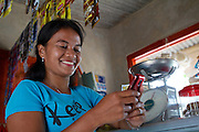 Jula Eha texting on her mobile phone in her shop outside the front of her house in a quiet residential area near the town of Bogor, Indonesia.<br /> <br /> Her shop had mixed success at first and she used to become demotivated, but after subscribing to Usaha Wanita she regained her motivation and started to think of more creative ways to make her business a success. <br /> <br /> As a result her profits have increased and she is now saving money in an education fund for her children. <br /> <br /> She has also been able to follow Usaha Wanita's advice on savings and investments and she has joined a savings scheme and purchases new fridges and display cabinets for her store.