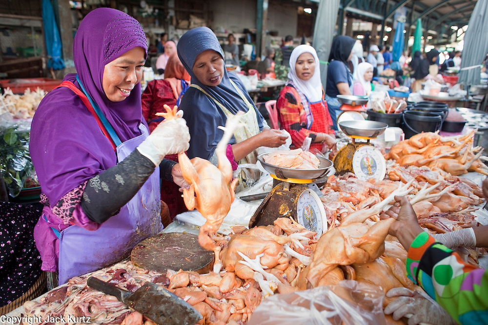 """Sept 25, 2009 -- PATTANI, THAILAND: Muslim women butcher chickens for customers in the morning market in Pattani, Thailand. Thailand's three southern most provinces; Yala, Pattani and Narathiwat are often called """"restive"""" and a decades long Muslim insurgency has gained traction recently. Nearly 4,000 people have been killed since 2004. The three southern provinces are under emergency control and there are more than 60,000 Thai military, police and paramilitary militia forces trying to keep the peace battling insurgents who favor car bombs and assassination.  Photo by Jack Kurtz / ZUMA Press"""