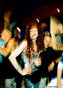 Transvestite wearing a long red wig and glitzy silver dress pulling a funny face, Ibiza, 1999