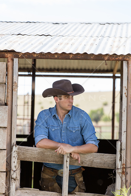 good looking cowboy taking a break in a barn