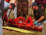 Paramedics try to assess the condition of boat racer Shane Venier of LaSalle, Michigan prior to tranporting him to Northern Michigan Hospital in Petoskey.  Shane and his wife Julie (not pictured) were both injured when they collided with a boat that was tied along the shore during the 2007 Top O' Michigan Marathon Nationals in Indian River.