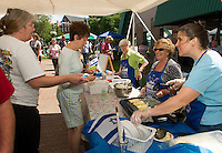 Tammy Fontaine and Dot Faulkner stop at the Israeli table for a freshly made strawberry blintz prepared by Karen Rimes, Irene Gordon and Joyce Selig during Laconia's annual Multicultural Market Festival on Saturday.   (Karen Bobotas/for the Laconia Daily Sun)