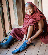 Novice Buddhist monk putting his socks on to play soccer (Myanmar)