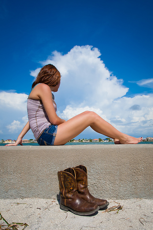 ST. PETERSBURG, FL -- Cowboys boots take a pause as a sun-worshipper takes in the sun while fishing along the seawall at Pass-A-Grille.  (PHOTO / CHIP LITHERLAND)