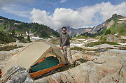Adult male at backcountry campsite. Yellow Aster Butte Basin, Mount Baker Wilderness. Mount Shuksan is in the distance. North Cascades Washington