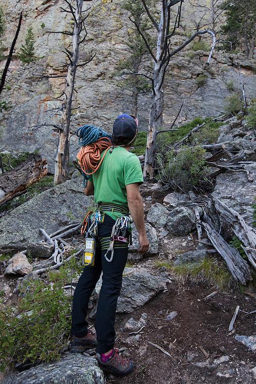 climbing guide Brett Bloxom assess the climb for a night of cliff camping in Estes Park, Colorado.