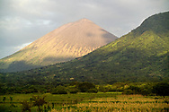 Light peers through the clouds to grace the volcano in the San Cristobal Volcanic Complex in Nicaragua. This active volcanic region has recorded constant activity since 1999. It is part of Los Maribios, 60 km spine of 21 volcanoes, 5 of which are active. The area is home to dry tropical forest and numerous rustic farms.