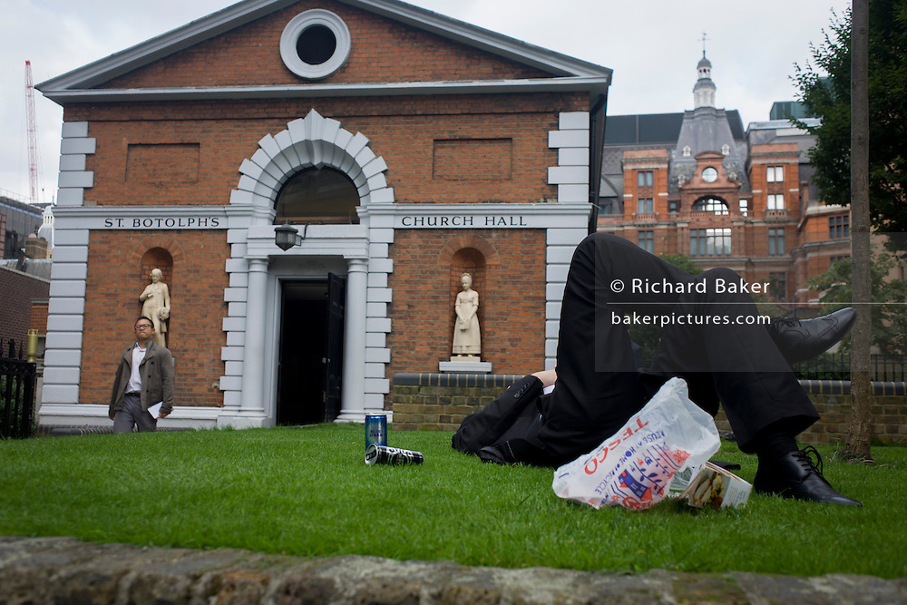A city worker relaxes during lunchtime outside St Botolph's Church Hall. Originally an infants' school, St Botolph's Church Hall stands in the churchyard of the Church of St Botolph-without-Bishopsgate. The entrance to the hall is flanked by two Coade stone statues of a schoolboy and schoolgirl wearing 19th century costume.