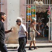 Cubans manage their daily life waiting for overcrowded busses, doubling up on old classic cars and motorcycles or walking everywhere. Locals walk and shop in La Habana Vieja. <br /> Photography by Jose More
