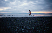 Man running at sunset on beach Seattle Washington USA&#xA;<br />