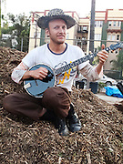 "Silver Lake, Los Angeles, California: Film director Charles Wurmwood is a volunteer organizer (and Silver Lake ""councilman at large"") of the Micheltorena School and Community Garden. Here he sits on a pile of mulch, strumming his banjo while people grab free seedlings (photo: Ann Summa)."