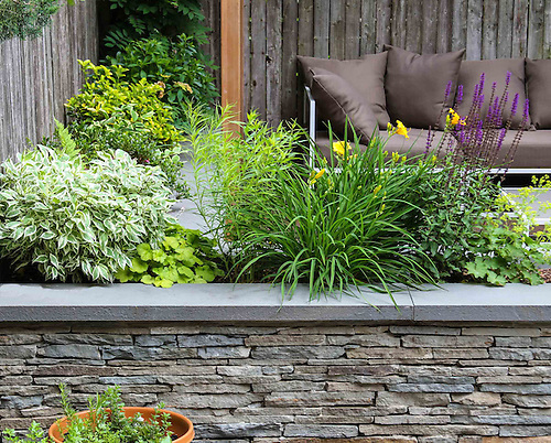 Modern Garden Featuring Traditional Stacked Stone Seating Wall And Cedar  Pergola With Planting For Seasonal Interest