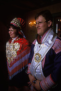 Bride and groom in traditional costumes at a Sami wedding in Kautokeino, Norway. The newly-wed couple emerge from the church to greet their friends and relatives, the bride wearing a glittering array of silver brooches.