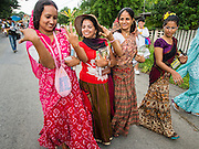 31 AUGUST 2014 - SARIKA, NAKHON NAYOK, THAILAND: Hindu women dance in the street during a parade to honor Ganesh at Shri Utthayan Ganesha Temple in Sarika, Nakhon Nayok. Ganesh Chaturthi, also known as Vinayaka Chaturthi, is a Hindu festival dedicated to Lord Ganesh. It is a 10-day festival marking the birthday of Ganesh, who is widely worshiped for his auspicious beginnings. Ganesh is the patron of arts and sciences, the deity of intellect and wisdom -- identified by his elephant head. The holiday is celebrated for 10 days, in 2014, most Hindu temples will submerge their Ganesh shrines and deities on September 7. Wat Utthaya Ganesh in Nakhon Nayok province, is a Buddhist temple that venerates Ganesh, who is popular with Thai Buddhists. The temple draws both Buddhists and Hindus and celebrates the Ganesh holiday a week ahead of most other places.    PHOTO BY JACK KURTZ