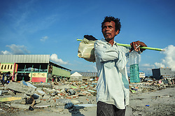 October 3, 2018 - Palu, Central Sulawesi, Indonesia - Darwis (53) walks in the village area that was destroyed after the earthquake..A deadly earthquake measuring 7.7 magnitude and the tsunami wave caused by it has destroyed the city of Palu and much of the area in Central Sulawesi. According to the officials, death toll from devastating quake and tsunami rises to 1,347, around 800 people in hospitals are seriously injured and some 62,000 people have been displaced in 24 camps around the region. (Credit Image: © Hariandi Hafid/SOPA Images via ZUMA Wire)