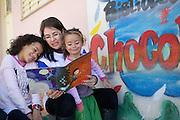 C&A volunteers reading with some of the children who attend C&A Instituto library called 'Biblioteca Chocolatao'.