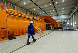 An RWE employee walks past the generator at left, which is driven by the giant turbine in the background, at the RWE nuclear power plant, in Lingen, Germany, on Tuesday, Sept. 6, 2011. (Photo © Jock Fistick)