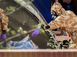 © Licensed to London News Pictures. 06/07/2018. Amesbury, UK. A police officer in a protective suit and gas mask throws a piece of plastic in a bin after gathering evidence inside a house in Muggleton Road, Amesbury where a couple, named locally as Dawn Sturgess, 44, and her partner Charlie Rowley, 45, were taken ill on Saturday 30th June 2018. Police have confirmed that the couple have been in contact with Novichok nerve agent. Former Russian spy Sergei Skripal and his daughter Yulia were poisoned with Novichok nerve agent in nearby Salisbury in March 2018. Photo credit: Peter Macdiarmid/LNP