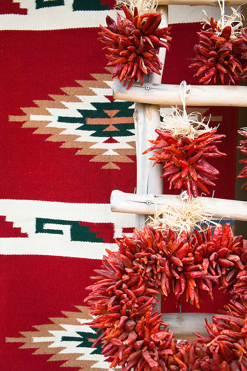 Chile ristras hung on a pueblo ladder in front of a Native American Indian blanket. Taos, New Mexico.
