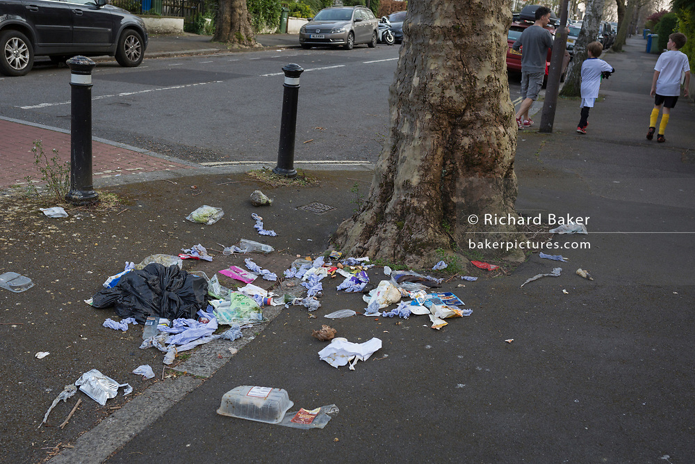 As the UK Prime Minister Boris Johnson suffers from Coronavirus and remains in intensive care in hospital - with a record 938 UK daily deaths recorded, a total of 7,097, Londoners keep to government guidelines for daily exercise while walking past a rubbish bag torn open by an urban fox in Herne Hill, Lambeth, on 8th April 2020, in south London, England.