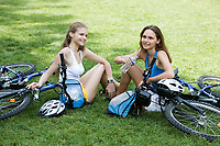 two young beautiful woman are visiting paris in summer with bicycle