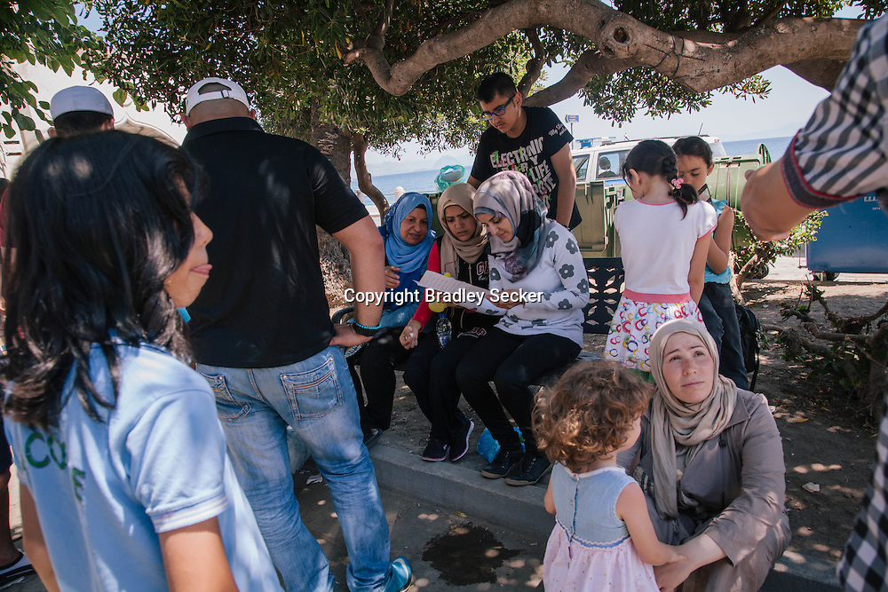 Irregular migrants sit outside the police station in Kos town, Kos island, Greece. People await registration with Greek authorities after arriving from Turkey in the early hours of the morning, and then to progress their journey further into western Europe.