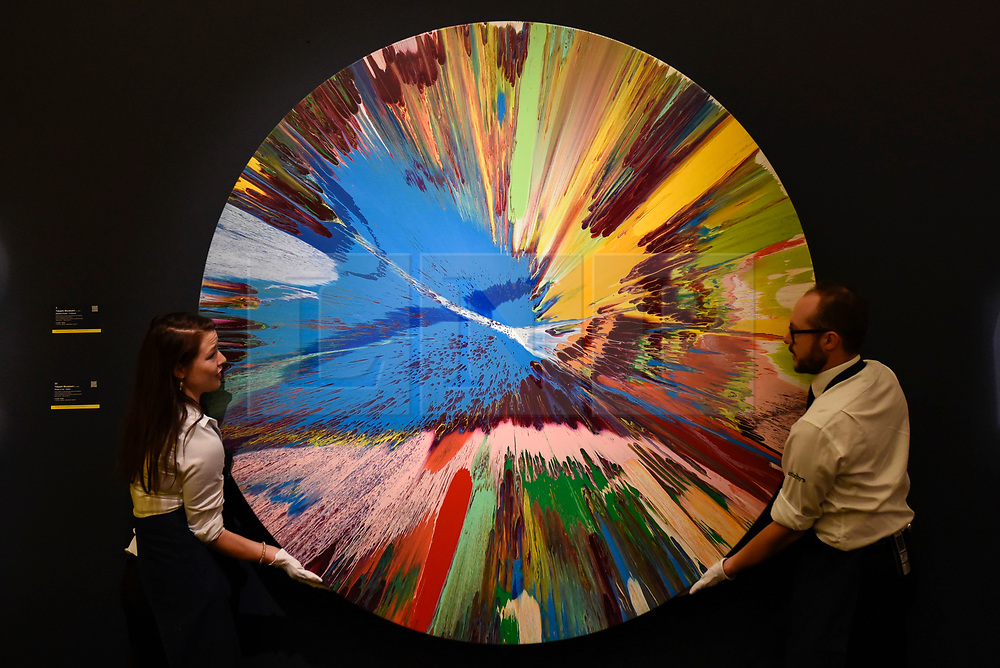 """© Licensed to London News Pictures. 14/09/2018. LONDON, UK. Technicians inspect """"beautiful all round, big toys for big kids, Frank and Lorna, when we are no longer children we are already dead, painting"""", 1998, by Damien Hirst (Est. GBP150,000-200,000) at a preview of the """"Yellow Ball: The Frank and Lorna Dunphy Collection"""" sale at Sotheby's in New Bond Street.  Frank Dunphy was Damien Hirst's former business manager and mentor.  Over 200 works will be auctioned by Sotheby's on 20 September 2018.  Photo credit: Stephen Chung/LNP"""