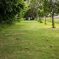 Helmingham Hall gardens in Suffolk England. The Apple Walk with two elderly visitors sitting on a bench.