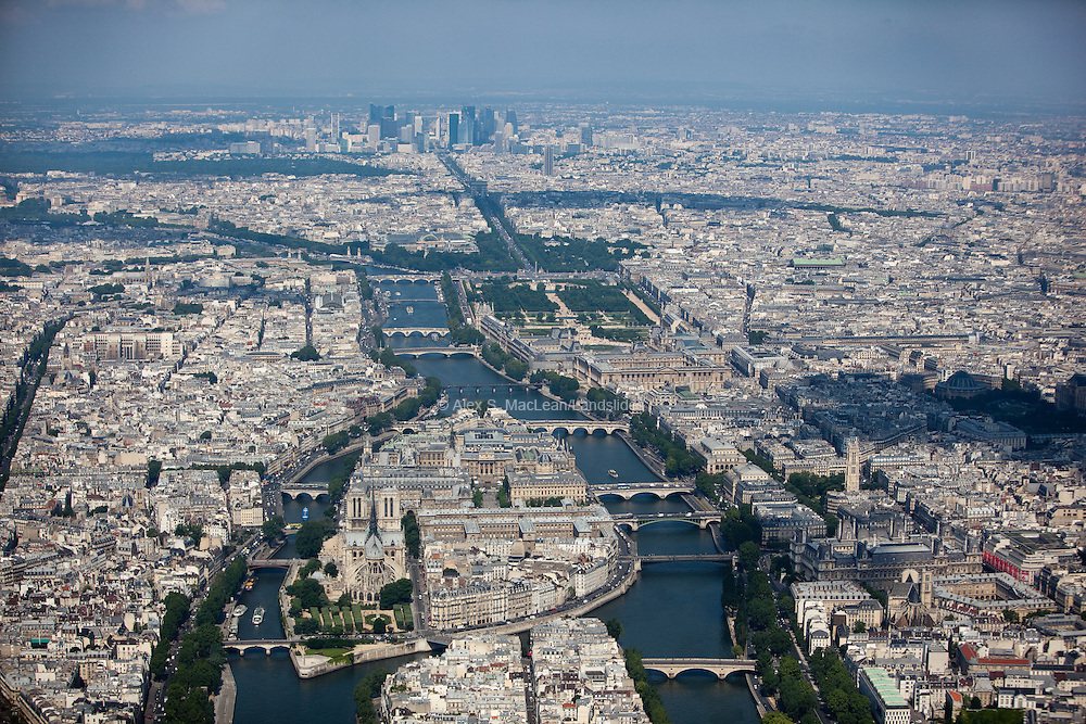 Looking down the Left and Right Banks of the Seine with Ile Saint-Louis and Ile de la Cité, and Notre Dame and numerous bridges linked to the city. In the background is the Arc du Triomphe and the Grande Arche de la Defense.