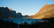 "Sunrise light hits Going-to-the-Sun Mountain and Little Chief Mountain in the Lewis Range above Saint Mary Lake (4484 feet / 1367 meters elevation) in Glacier National Park, Montana, USA. The Going-to-the-Sun Road runs along the north shore. Here the great plains end and the Rocky Mountains abruptly rise 5000 feet above the lake. Since 1932, Canada and USA have shared Waterton-Glacier International Peace Park, which UNESCO declared a World Heritage Site (1995) containing two Biosphere Reserves (1976). Rocks in the park are primarily sedimentary layers deposited in shallow seas over 1.6 billion to 800 million years ago. During the tectonic formation of the Rocky Mountains 170 million years ago, the Lewis Overthrust displaced these old rocks over newer Cretaceous age rocks. Glaciers carved spectacular U-shaped valleys and pyramidal peaks as recently as the Last Glacial Maximum (the last ""Ice Age"" 25,000 to 13,000 years ago). Of the 150 glaciers existing in the mid 1800s, only 25 active glaciers remain in the park as of 2010, and all may disappear by 2020, say climate scientists. (Panorama stitched from 2 overlapping images.)"