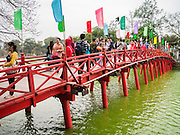 31 MARCH 2012 - HANOI, VIETNAM:   Tourists cross a wooden bridge to Ngoc Son Temple, which was reportedly built during the Tran Dynasty (ca 1225) in the Old Quarter of Hanoi, Vietnam. The temple is dedicated to Tran Hung Dao, a Vietnamese national hero who defeated an invading Mongol army in the 13th century.  PHOTO BY JACK KURTZ