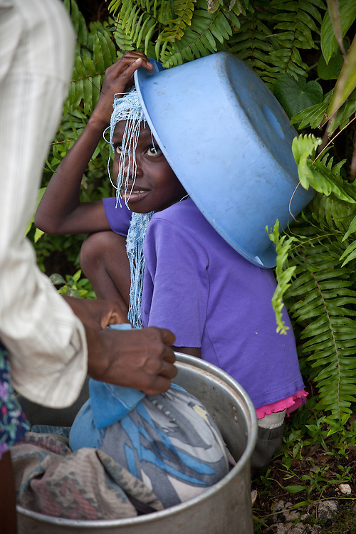 A girl peeks out from beneath a basin at a market near Caye Michel in the Massif de la Hotte, Haiti
