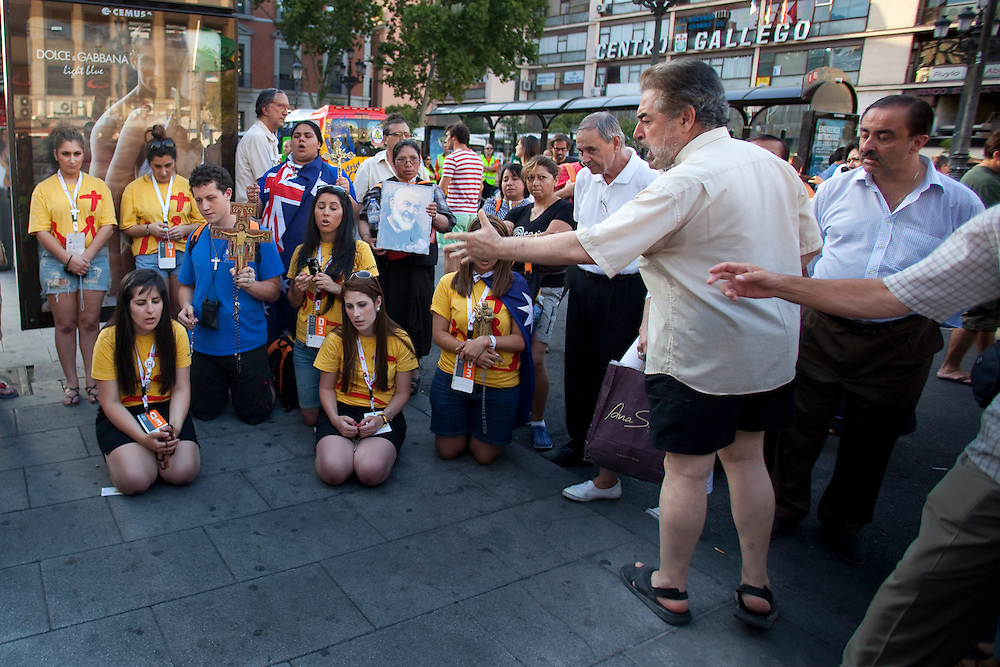 Pilgrims pray in the street during a protest against the next Pope Benedict XVI visit in Madrid on Wednesday, Aug. 17, 2011. Pope Benedict XVI is due to arrive Thursday for a nearly four-day visit to celebrate World Youth Day, and thousands of protesters railing against his visit marched through central Madrid to the central Sol plaza where they have held months of demonstrations against the government's anti-austerity policies. .