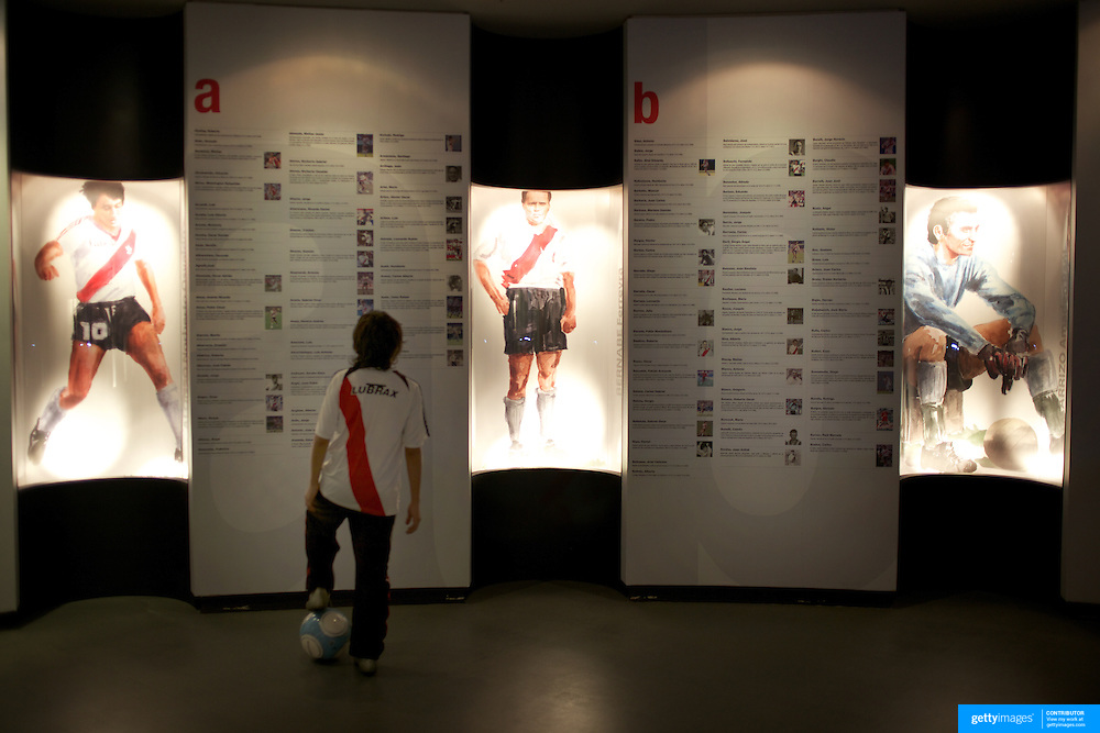 A young River Plate fan, complete with football, reads historical facts in the museum at River Plates' El Monumental stadium, Buenos Aires, Argentina, 25th June 2010. Photo Tim Clayton..