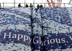 "© Licensed to London News Pictures. 30/05/2012. London, UK Workmen hang a huge banner with a giant Union Flag on it reading 'Happy, Glorious, Victorious"" on the side of a building in Piccadilly. Preparations today 20th May 2012 around London ahead of The Queen's Diamond Jubilee this weekend. Photo credit : Stephen Simpson/LNP"