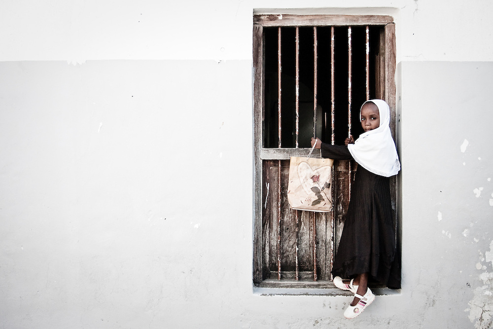 A young girl hangs fromthe barred windows of a mosque in Stonetown, Zanzibar