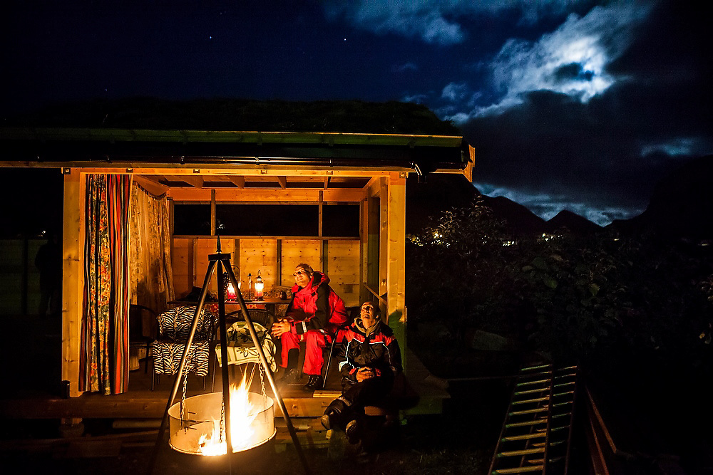 Bjornar Hogset (left) and Parmenter Welty, seated around a campfire, watch the night sky from Bjørnar's home in Sorland, Vaeroy Island, Lofoten Islands, Norway.