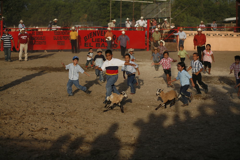 Julia Robinson photo.Children race to be the first to catch a goat during a break from bull riding at El Bajio in Von Ormy, Texas.