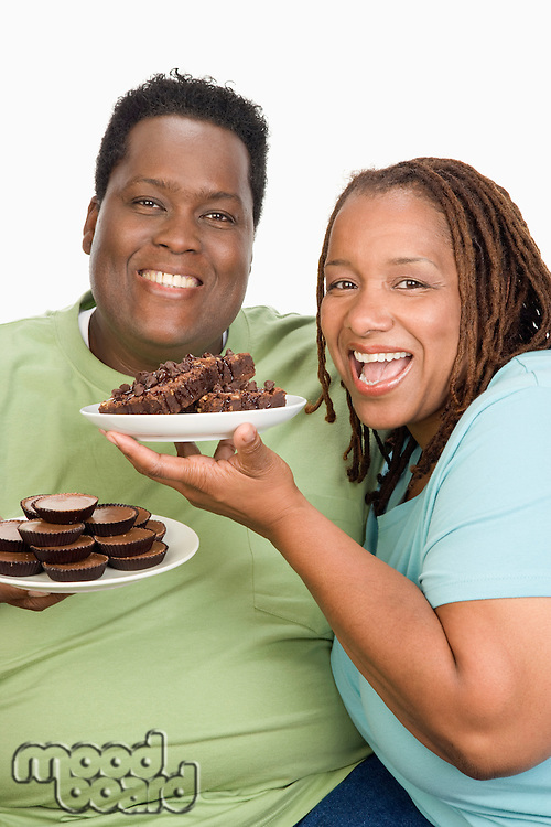 Mid-adult overweight woman and mid-adult overweight man holding plates with cookies