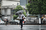 Man walking under the rain. Typhoon number 10 called Lionrock hit japan early on morning, in Tokyo. 30/08/2016-Tokyo, JAPAN