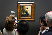 Taking iPhone smartphone photograph of painting by Johannes Vermeer 'The Milkmaid' at Rijksmuseum, Amsterdam, Holland