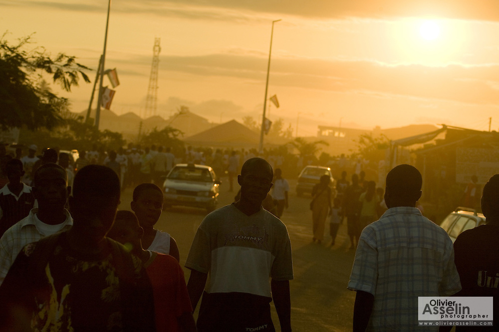 People walk along a street at sunset as they depart the fair grounds after a day of festivities during the annual Oguaa Fetu Afahye Festival in Cape Coast, Ghana on Saturday September 6, 2008.