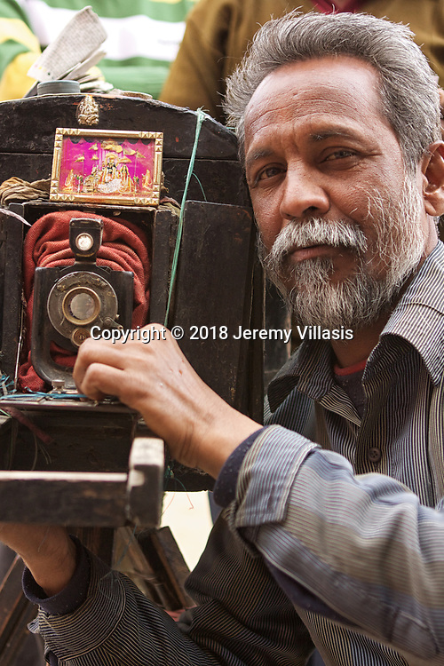 Surendar Chand, Tikam's brother, poses with an 1860 Carl Zeiss camera - the last of its kind in the world today. He alternates with Tikam in taking photos of tourists near the entrance of Hawa Mahal in Jaipur everyday.