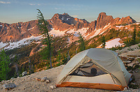Backpacking tent at daybreak on ridge above Cutthroat Pass, near Pacific Crest trail. Cutthroat Peak is in the distance. North Cascades Washington