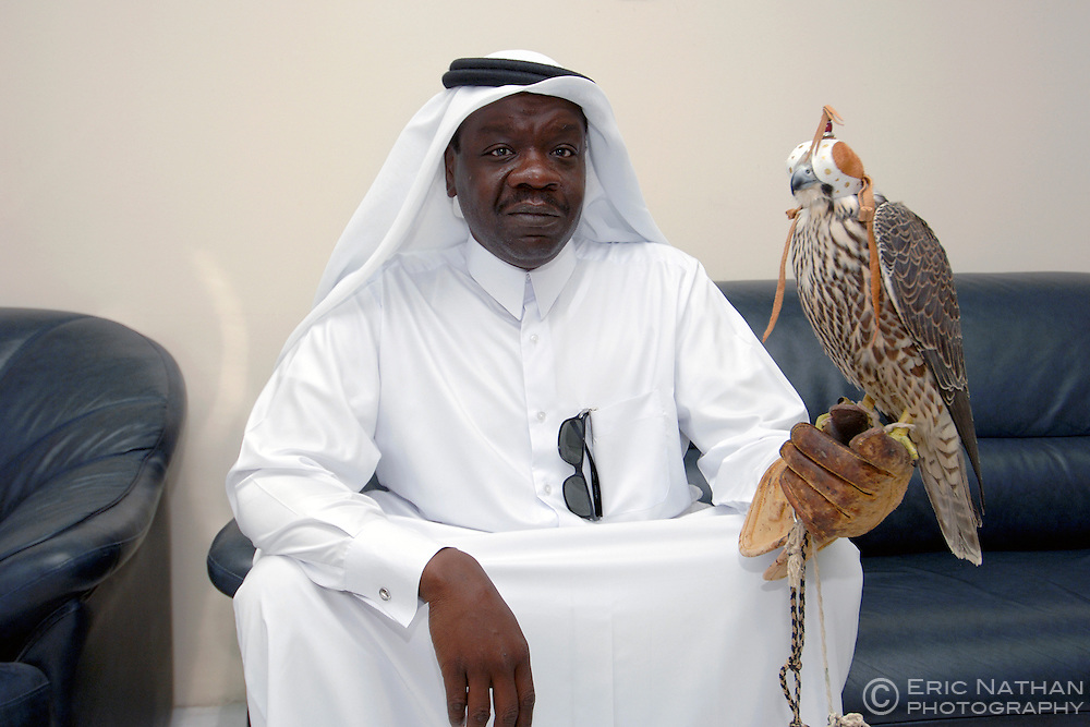 A Qatari poses with his hooded falcon in the waiting room of the falcon veterinary clinic in Doha, the capital of Qatar.