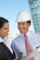 Businessman in hardhat showing clipboard to businesswoman